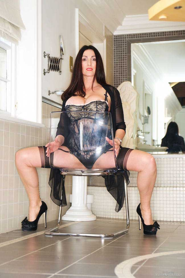 Long legs seamed stockings and high heels Miss Hybrid flashes her pussy through the perspex chair.